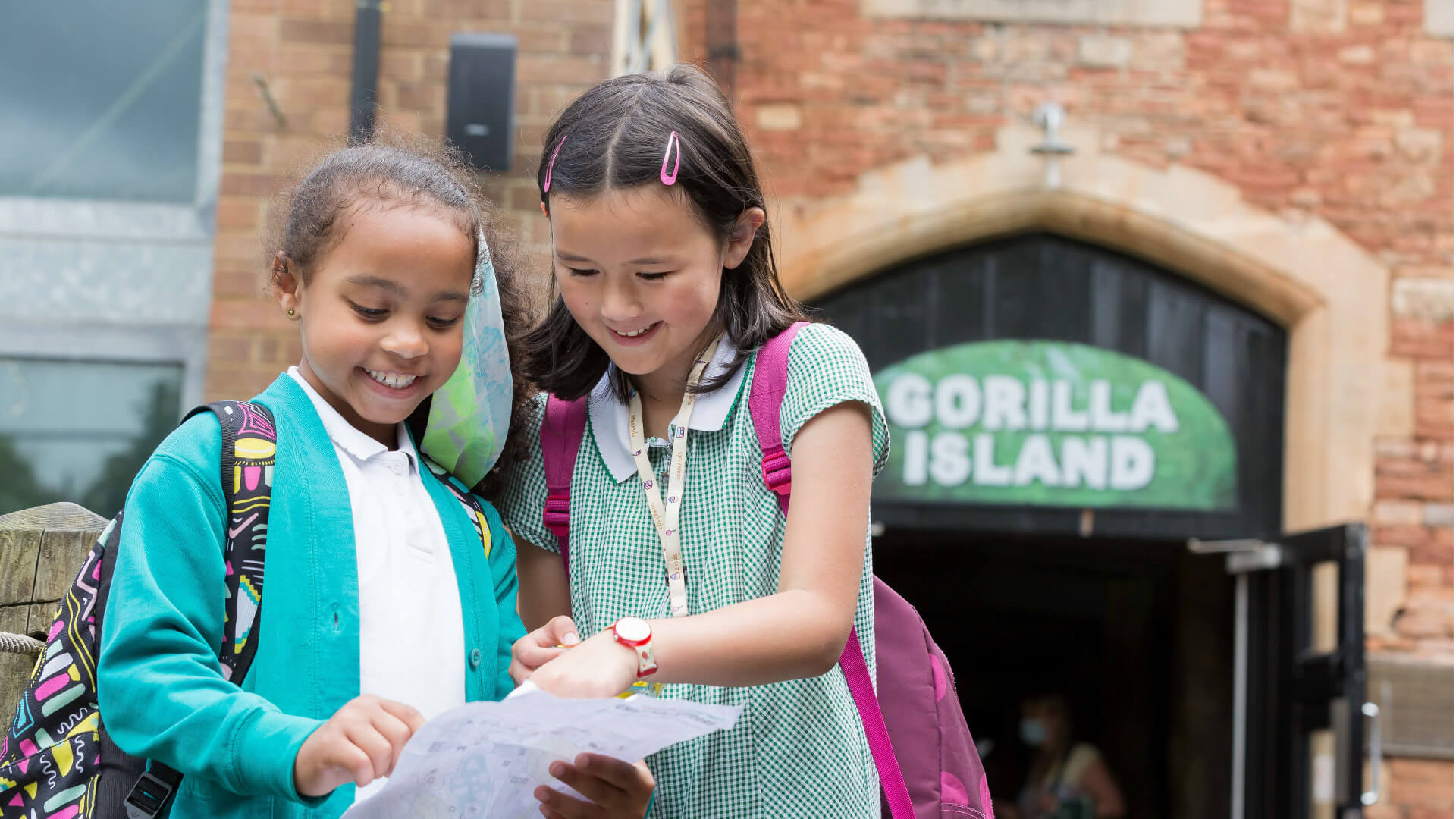 Two young primary school girls looking at a trail leaflet in front of Gorilla Island at Bristol Zoo Gardens