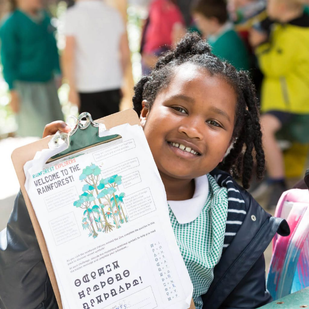 A young girl smiling and holding a zoo activity sheet