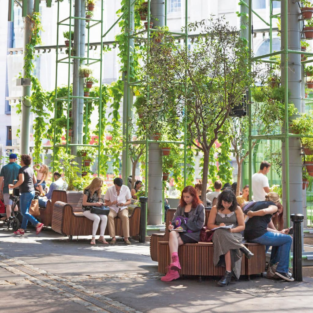 People in spacious, airy waiting hall with hanging plant pots and fresh looking foliage