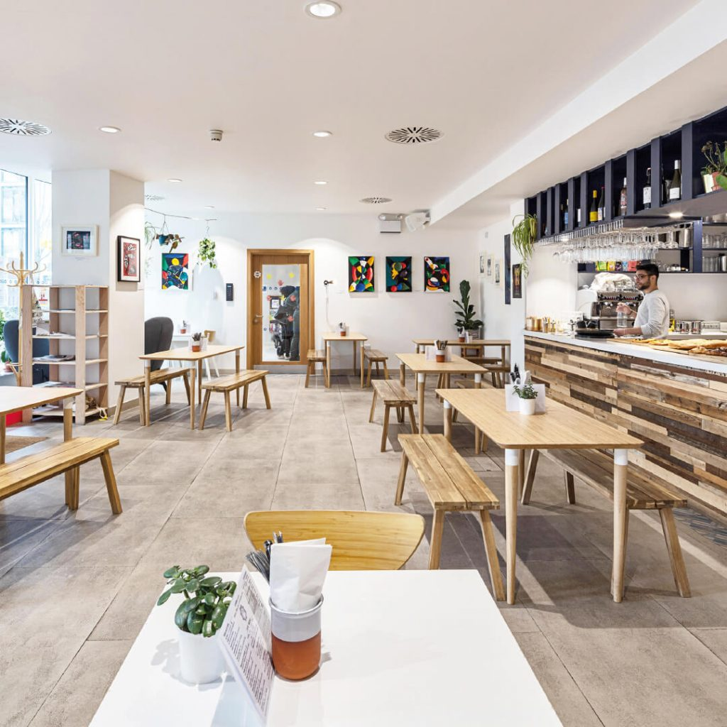 Spacious light cafe with benches and tables