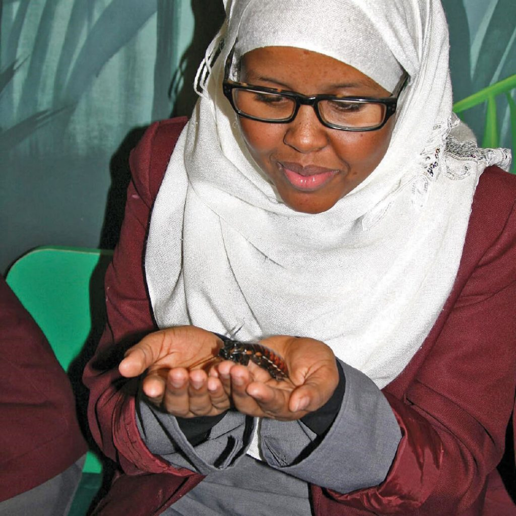 Student holding a hissing cockroach during an education session at Bristol Zoo Gardens