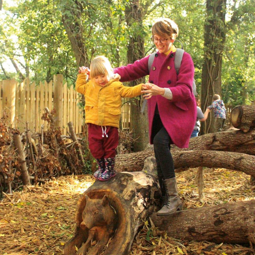 Child balancing on log, held by parent on adventure playground at Bear Wood