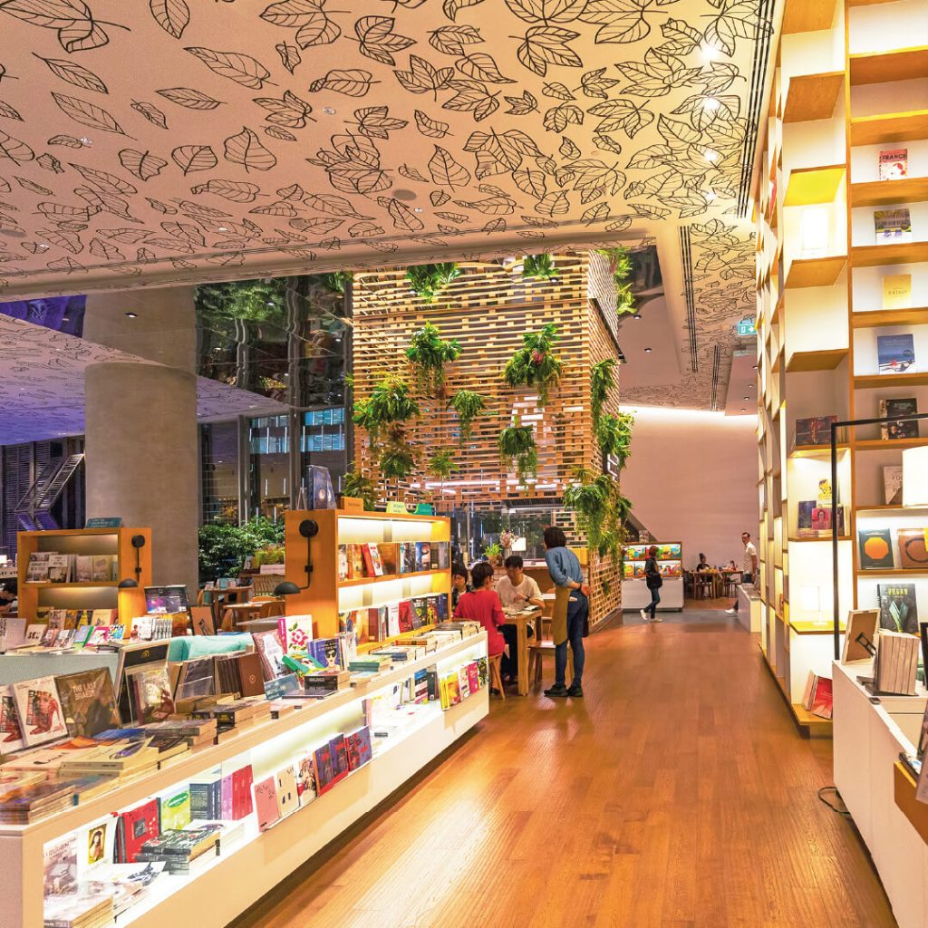 Spacious shop with books on display and potted plants on walls